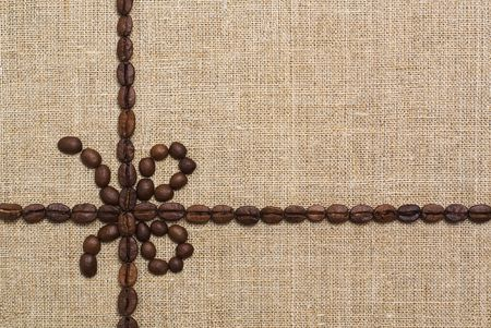 Gift pattern made of fried coffee beans on grunge canvas