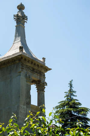enviroment: Small ancient steeple, with column e capital, arounded by green enviroment.