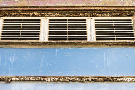 urban decay: old metal vents with grating, factory North of Italy