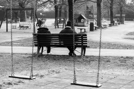 adult toys: Senior couple sitting on a bench in a playground