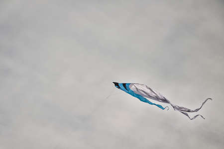 cloudy sky: Colorful kite flying in a cloudy sky