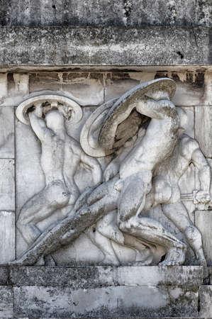 escultura romana: Bajo relieve y la escultura de los antiguos soldados romanos con escenas de guerra, de mármol de Carrara Foto de archivo