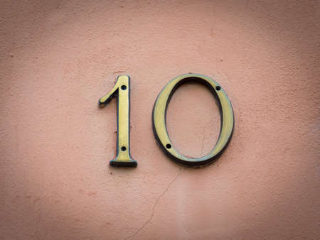 number ten: Gold house number ten on a pink background.