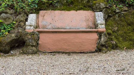 antique furniture: Ancient brown stone bench stuck in the rock