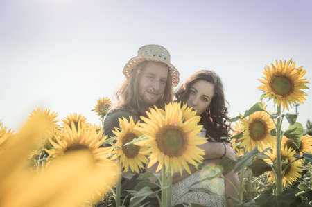graying: Young happy and romantic caucasian couple at sunflowers field