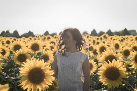 graying: Young caucasian woman with long hairs among sunflowers field