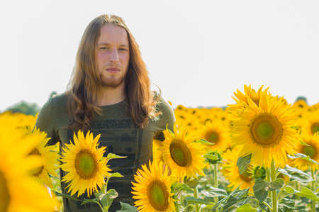 graying: Young caucasian woman with blond hair and long hair at sunflowers field