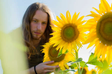 Young caucasian woman with blond hair and long hair at sunflowers field