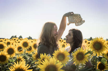 graying: Happy Spontaneous Attractive Young Couple Share a good joke laughing uproariously and hugging each other outdoors in an sunflower field