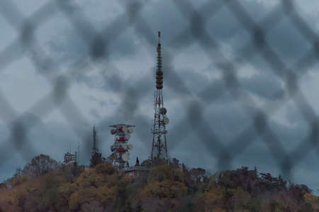 Telecommunication Radio Antenna and Satelite Tower with blue sky behind a chain fence