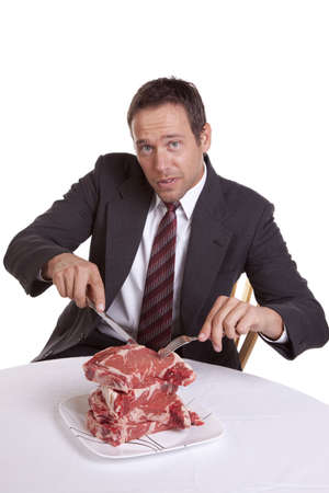 A man with a large pile of big steaks looking up.