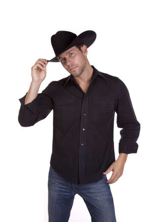 cowboy hat: a man in his black cowboy hat tiping it with his fingers saying hello.