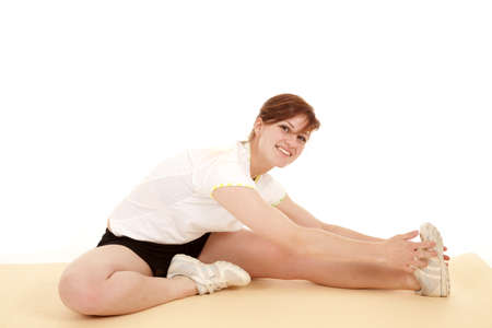 A woman stretching out her legs with  a smile on her face. photo