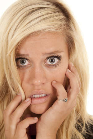 A close up of a woman's face with a scared or shocked expression on her face. photo