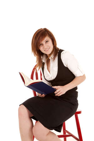 A woman sitting in a chair with a book opened. photo