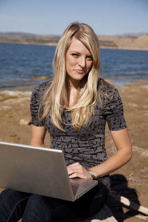 A woman sitting by the water in the outdoors working on her computer with a smile on her face. photo