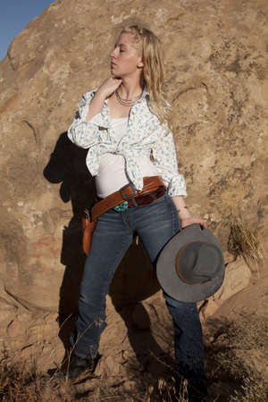 A woman with her eyes closed in her western outfit holding on to her hat. photo