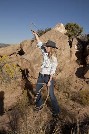 A woman swinging her rope in the outdoors. photo