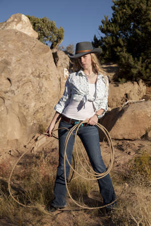 A cowgirl standing and holding on to her rope in the outdoors with a serious expression on her face.