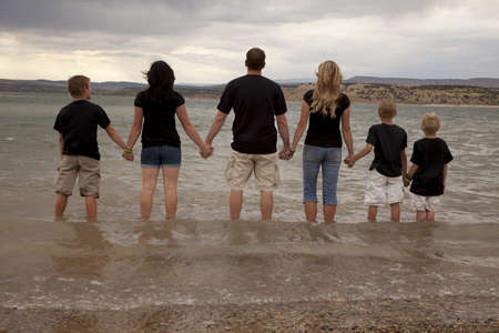 A back vew of a father, mother, and children holding hands and standing in the water together.