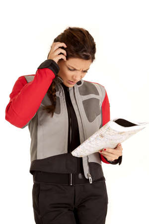 A woman looking at a road map for directions with  a confused and frustrated expression on her face. photo