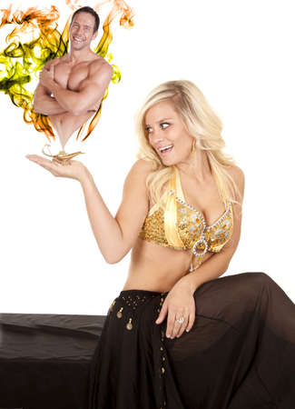 lady with the lamp: a female genie holding her golden lamp in her hand with smoke and a man coming out of the lamp. Stock Photo