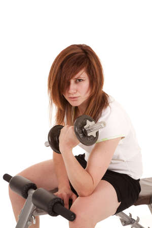 A woman sitting on a weight bench working out her arms. photo