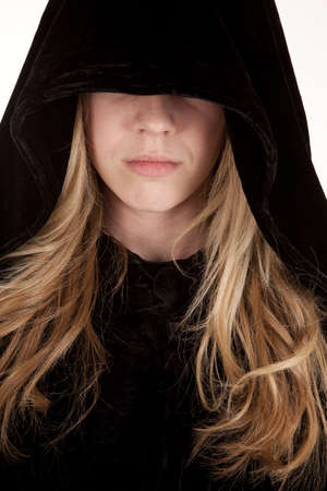 cloak: A girl with a hood over her eyes with a sad expression on her face. Stock Photo