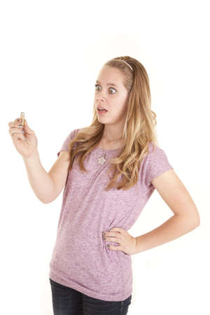 A girl looking at a guns bullet with a scared expression on her face. photo