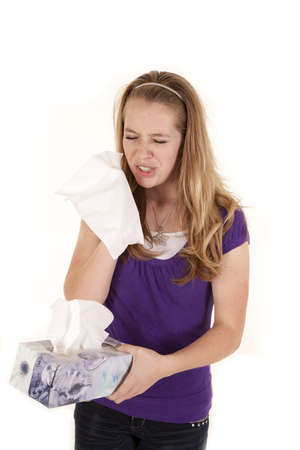 A teenage girl holding a box of tissues getting ready to sneeze. photo
