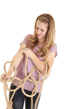 A girl all tangled up in a rope trying to get out. photo