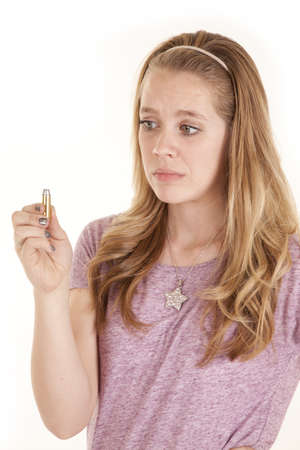 A girl holding on to a bullet with a  unsure expression on her face. photo