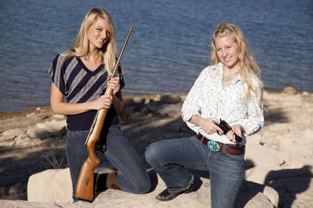 two women kneeling down on the rocks holding on to their weapons. photo