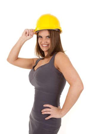 een vrouw in haar grijze kostuum draagt haar bouw hoed met een glimlach op haar gezicht.