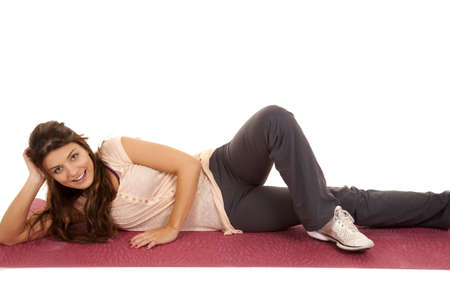 A woman laying on her yoga mat stretching with a smile on her face. photo