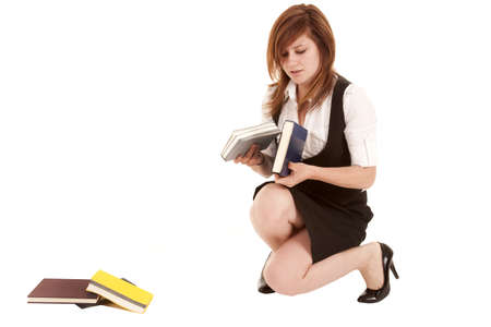 uniform skirt: A woman picking up her books off of the ground.