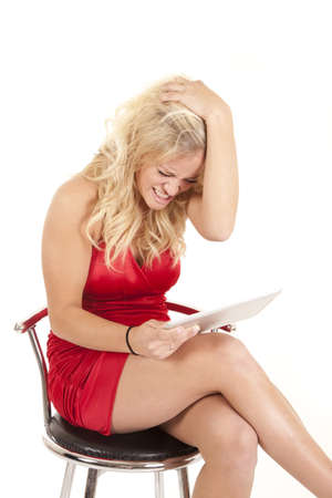 a woman in her red dress holding on to her reader mad and frustrated. Stock Photo - 12104841