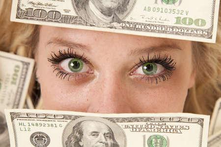 A woman with green eyes peeking through money