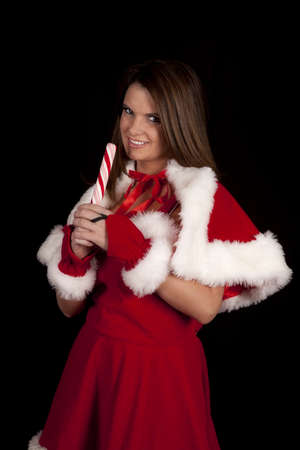 a woman in her Mrs. Santa Clause outfit licking a red and white striped peppermint stick. photo
