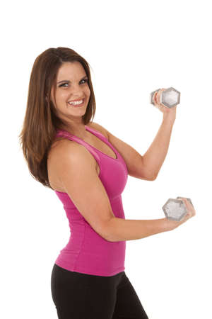 A woman in her pink tank lifting weights with a smile on her face. photo