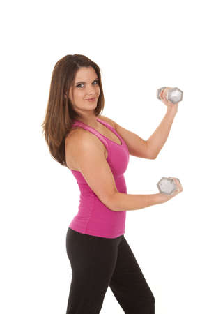 A woman lifting weights with a smile on her face. photo