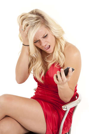 A woman in her red dress upset at her phone. photo