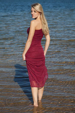 A woman walking in the water in her red formal looking over her shoulder. photo