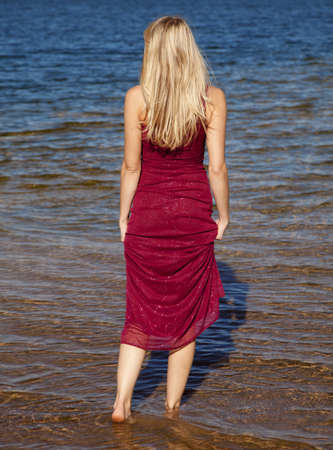 A woman in her red formal walking in the water. photo