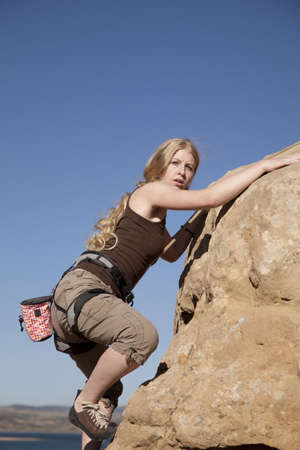 A woman rock climbing with a  serious expression.