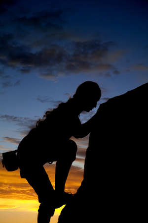 A silhouette of a woman rock climbing with a beautiful sunset in the back ground.