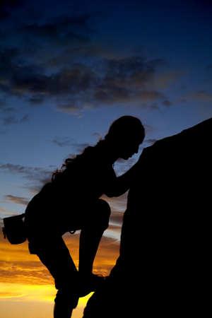 pnacze: Sylwetka skały kobiety wspinaczka z pięknym zachodem słońca w tylnej ziemi.