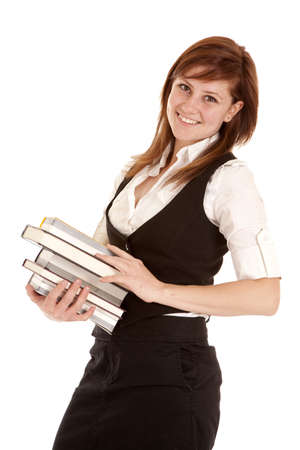 A woman holding on to her stack of books with a smile on her face. Фото со стока