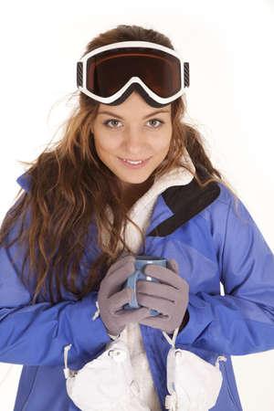 彼女のスキーの女性服し、彼女の顔に笑みを浮かべてホット チョコレートのマグカップを保持しているゴーグルします。 写真素材
