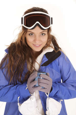 a woman in her ski clothes and goggles holding a mug of hot chocolate with  a smile on her face. Stock Photo